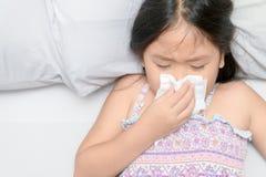 Aziatisch meisje die de neus blazen door weefsel stock afbeeldingen