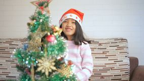 Aziatisch meisje die een Kerstboom verfraaien en met geluk dansen stock videobeelden