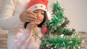 Aziatisch meisje die een Kerstboom verfraaien en voor beste thingHappy Aziatisch meisje bidden die een Kerstboom met h verfraaien stock video