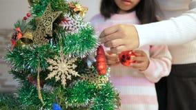 Aziatisch meisje die een Kerstboom verfraaien en voor beste thingHappy Aziatisch meisje bidden die een Kerstboom met h verfraaien stock footage