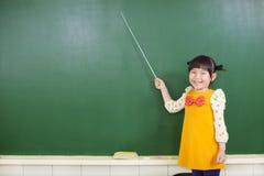 Aziatisch meisje die een knuppel met behulp van om te richten Stock Foto's