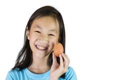 Aziatisch meisje die en een ei glimlachen houden stock fotografie