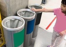Aziatisch meisje die gebruikt document in gerecycleerde bak zetten verschillend stock afbeelding