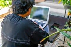 Aziatisch meisje die laptop in de tuin met behulp van stock fotografie