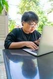Aziatisch meisje die laptop en smartphone gebruiken stock afbeeldingen
