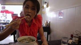 Aziatisch meisje die noedel in een lokaal restaurant eten, phnom penh stock footage