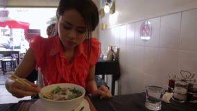 Aziatisch meisje die noedel in een lokaal restaurant eten, phnom penh stock videobeelden