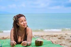 Aziatisch meisje die op de oceaankust liggen die naast een kokosnoot glimlachen royalty-vrije stock foto