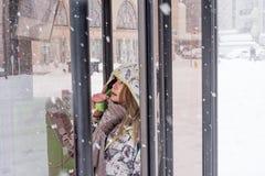 Aziatisch meisje die openbare telefoon in sneeuw met behulp van Stock Foto