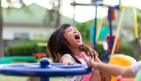 Aziatisch meisje die pret het spelen op carrousel hebben stock foto