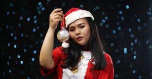 Aziatisch Meisje die Santa Costume Holding Christmas Bauble dragen royalty-vrije stock afbeelding