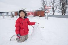 Aziatisch meisje die sneeuwman, Zwitserland, Europa maken stock afbeelding