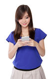 Aziatisch meisje die terwijl texting, geïsoleerd op wit glimlachen Royalty-vrije Stock Foto's