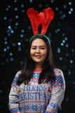 Aziatisch Meisje die van het Kerstmissweater en Rendier Hoornenhoofdband dragen royalty-vrije stock fotografie