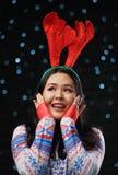 Aziatisch Meisje die van het Kerstmissweater en Rendier Hoornenhoofdband dragen stock foto's