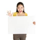 Aziatisch meisje die witte lege document kaart houden stock foto