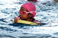 Aziatisch meisje die in zwembad zwemmen stock foto's