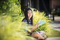 Aziatisch meisje en schoolboek ter beschikking toothy het glimlachen gezicht met happ Royalty-vrije Stock Foto's