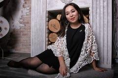 Aziatisch meisje in gescheurde nylonkousenzitting dichtbij de open haard met de sjaal op zijn schouders Royalty-vrije Stock Foto