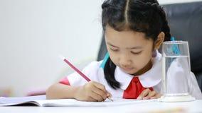 Aziatisch meisje in het Thaise eenvormige doende dicht omhoog geschoten het huiswerk van de kleuterschoolstudent stock footage