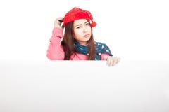 Aziatisch meisje met rode Kerstmishoed in slechte stemmingstribune achter een bla Royalty-vrije Stock Afbeeldingen
