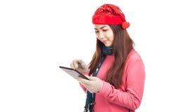 Aziatisch meisje met rode PC van de het gebruikstablet van de Kerstmishoed Stock Afbeeldingen