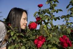 Aziatisch meisje met rode rozen Royalty-vrije Stock Foto's