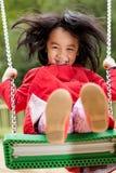 Aziatisch meisje op een schommeling Stock Afbeeldingen