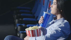 Aziatisch meisje in profiel het drinken soda in een bioskoop stock footage
