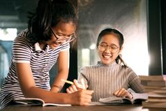 Aziatisch meisje twee die met gelukemotie lachen die het werk van het schoolhuis in woonkamer doen royalty-vrije stock afbeelding
