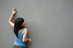 Aziatisch meisje wat betreft muur Stock Foto