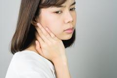 Aziatisch meisje in witte toevallige kledingsvangst dat, wegens de pijn van het harde werk steunt stock afbeelding
