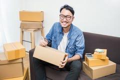 Aziatisch mens het schrijven adres op de doos stock afbeelding