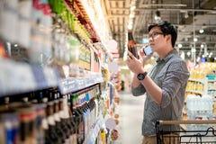 Aziatisch mens het winkelen bier die telefoon met behulp van royalty-vrije stock foto's