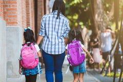 Aziatisch moeder en dochterleerlingsmeisje met de hand van de rugzakholding en samen het gaan naar school royalty-vrije stock foto's