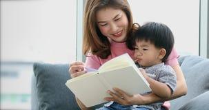 Aziatisch moeder en zoonslezingsboek samen stock videobeelden