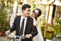 Aziatisch onlangs wed paar die een fiets berijden royalty-vrije stock fotografie