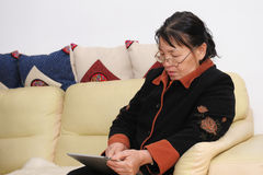 Aziatisch ouder wijfje met touchscreen tablet royalty-vrije stock afbeeldingen