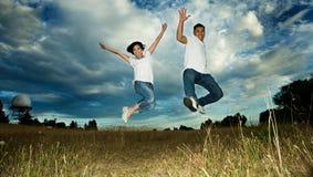 Aziatisch paar dat in vreugde springt Stock Foto's