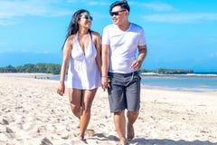 Aziatisch paar die op het strand van het tropische eiland van Bali, Indonesië lopen stock afbeelding