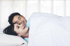Aziatisch paar die samen op het bed lachen stock foto