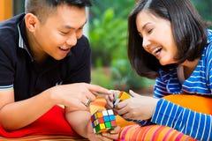 Aziatisch paar die thuis met magische kubus spelen stock foto's