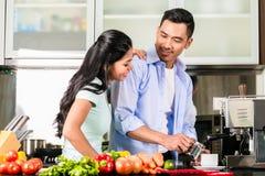 Aziatisch paar kokend voedsel samen in keuken Stock Afbeelding