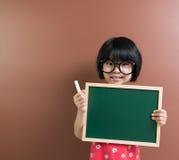 Aziatisch schooljong geitje met krijt en bord Royalty-vrije Stock Fotografie