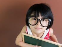 Aziatisch schooljong geitje met krijt en bord Stock Foto's