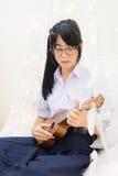 Aziatisch Thais middelbare schoolmeisje die in eenvormige glazen gitaar spelen Stock Fotografie