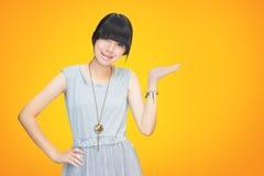 Aziatisch tienermeisje dat lege hand toont Stock Foto