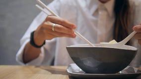 Aziatisch Toeristenmeisje die met Eetstokjes Traditioneel Tom Yam Noodle Soup in Restaurant eten 4K stock videobeelden