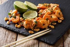 Aziatisch voedsel: sauteed garnalen met pinda's, kalk en kruidclose-up Stock Afbeelding