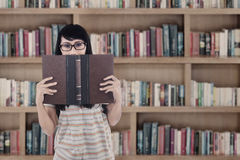 Aziatisch vrouwelijk student gelezen boek bij bibliotheek stock foto